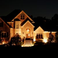 House at night with dramatic exterior lighting.